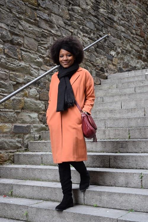 cuissardes-noires-manteau-orange-escalier