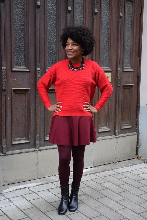 pull rouge flamboyant mains sur les hanchs